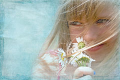 Little girl smelling daisy bouquet Stock Photo