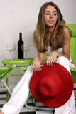 Summer breeze. Pretty young model holding red beach hat while sitting on green lounge chair Royalty Free Stock Photos