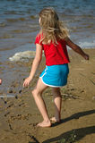Summer Breeze. Young girl stands on a lake shore feeling the summer breeze and wind comb threw her hair Royalty Free Stock Image