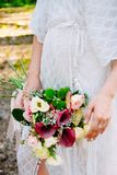 Summer bride. Bohemian styled wedding dress. Bouquet and sandals stock photography
