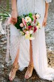 Summer bride. Bohemian styled wedding dress. Bouquet and sandals royalty free stock images