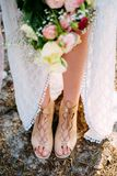 Summer bride. Bohemian styled wedding dress. Bouquet and sandals stock photos