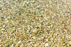 Beautiful delicated texture of little stones under the water, in Ibiza. Summer bright background of colorful pebbles while holidays at a beach in Ibiza. Green Stock Images
