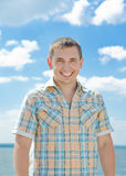 Summer bright smile. The young guy smiles against the blue sky broadly Stock Photo