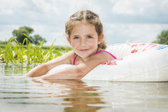 In summer, on a bright, sunny day on the river, a girl swims on Stock Photo