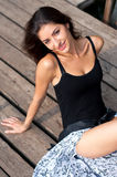 Summer brunette girl. Pretty young brunette woman in black leotard and skirt sitting on wooden dock and smiling Royalty Free Stock Photos