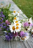 Summer bunch of flowers. Laying on the bench Royalty Free Stock Photo