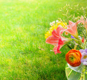 Summer bunch in glass vase with water on grass Stock Images