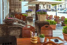 Garden restaurant in the summer. Tables and wicker chairs among the trees royalty free stock photo