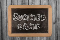 Summer camp. Blackboard frame with summer camp on wooden background Royalty Free Stock Image