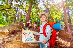 Little boy with treasure map in the forest game. Summer camp game boy with treasure map and other kids in the forest orienting stock image