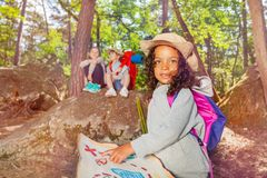 Summer camp orientation kids activities in forest. Summer camp game girl with treasure map and other kids in the forest orienting stock photo