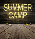 Summer Camp Sign. With a drawing on a natural rustic wooden wall from a country cabin outdoors as a symbol of recreation and fun education with a group of chalk stock illustration