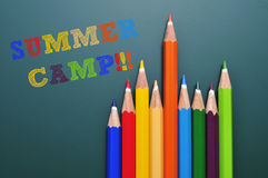 Summer camp. Text summer camp written on a chalkboard and some colored pencils of different colors Stock Photography