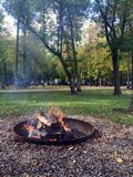 Summer campground campfire. One of the highlights of any camper`s summer, the open fire campsite.  Campers and campground trees in the background.  Smoke rising stock image