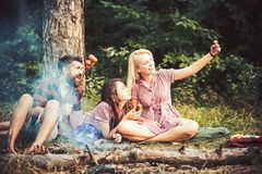 Summer camping. Blond lady taking selfie in wilderness. Smiling friends posing with sausages for photo. Summer camping, picnic in woods. Cheerful blond girl royalty free stock photography