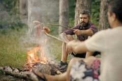 Summer camping, hiking, vacation. Picnic, barbecue, cooking food concept. Friends man roast sausages on sticks on campfire in forest royalty free stock image
