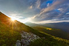 Summer Carpathian mountain, Ukraine. Last sun rays in evening sky with clouds above Syniak mountain. Summer sunset view from Homiak mountain, Gorgany, Carpathian Stock Photography