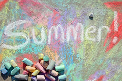 Summer in Chalk. The word summer is written in white sidewalk chalk with a colorful background drawing and lots of chalk scattered on the pavement Stock Photo