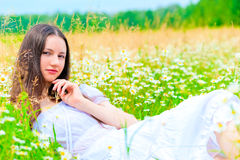 Summer chamomile field and resting girl Stock Image