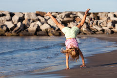Summer child. Little girl doing cartwheel by the ocean Royalty Free Stock Photo