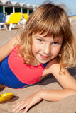 Summer child. Portrait of a little girl lying on sand at the beach stock image