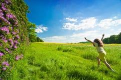 Summer Child. Girl running through summer field under blue sky - motion blur to child Stock Photos