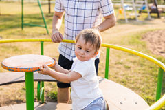 Summer, childhood, leisure and family concept - happy child and his father on children playground climbing frame Royalty Free Stock Photo