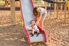 Summer, childhood, leisure and family concept - happy child and his mother on children playground climbing frame Stock Image