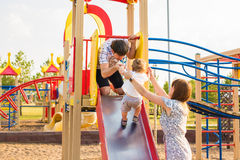 Summer, childhood, leisure and family concept - happy child and his parents on children playground climbing frame Royalty Free Stock Photography