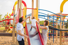 Summer, childhood, leisure and family concept - happy child and his parents on children playground climbing frame Stock Photo