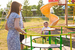 Summer, childhood, leisure and family concept - happy child and his parents on children playground climbing frame Stock Photos
