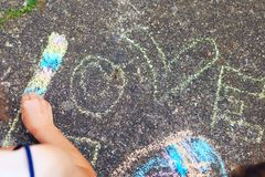 Summer, childhood, leisure and people concept - happy little Girl is drawing with chalks word Love royalty free stock photo