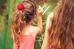 Summer, childhood, leisure and people concept - happy little Girls is drawing with chalks at summer park royalty free stock photo