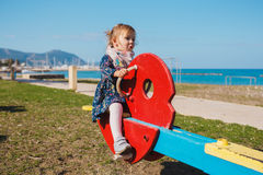 Summer, childhood, leisure and people concept - happy little girl on children playground Stock Photos