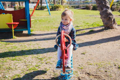 Summer, childhood, leisure and people concept - happy little girl on children playground Royalty Free Stock Photo