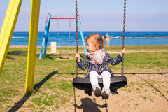 Summer, childhood, leisure and people concept - happy little girl on children playground Stock Images