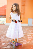 Summer, childhood and people concept - little girl on scooter Royalty Free Stock Photography