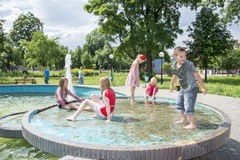 In the summer, children play in the fountain in the park. Stock Photo