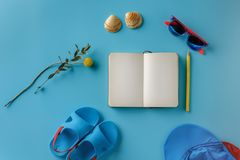 Summer children`s clothes and notebook on a bright blue background, top view. stock photography