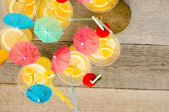 Summer citrus cocktail with umbrellas. Refreshing lemonade. royalty free stock photo