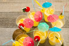 Summer citrus cocktail with umbrellas. Refreshing lemonade. royalty free stock photography