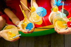 Summer citrus cocktails with umbrellas in the hands of girls. Re stock image