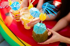 Summer citrus cocktails with umbrellas in the hands of girls. Re royalty free stock image