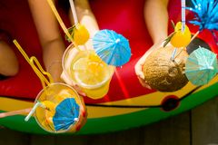 Summer citrus cocktails with umbrellas in the hands of girls. Re royalty free stock photography