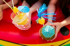 Summer citrus cocktails with umbrellas in the hands of girls. Re royalty free stock images