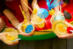 Summer citrus cocktails with umbrellas in the hands of girls. Re royalty free stock photos
