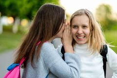 In summer city park. Two girl friends schoolgirls teenagers. Concept of joke, secret, fantasy, conversation, whisper. Surprise. Emotion of happiness is royalty free stock photos