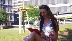 Summer in the city - a woman relaxes on the lawn in the park and reads a book. Urban Lifestyle - I have a lot of 4k footage on this topic and with this model stock footage