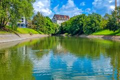 Summer cityscape – river surface with blue sky and green trees reflection. Summer cityscape – river surface with blue sky and green trees reflection Stock Image
